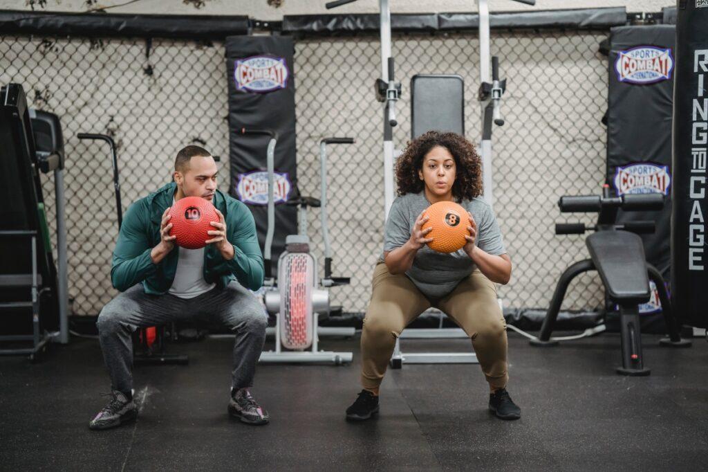man woman squat gym